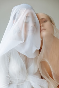 Portrait of two beautiful girls covered with light veil