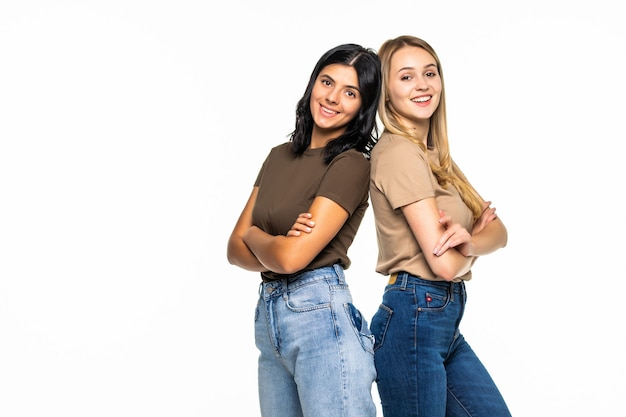 Ritratto di due belle ragazze in piedi schiena contro schiena isolate su un muro bianco