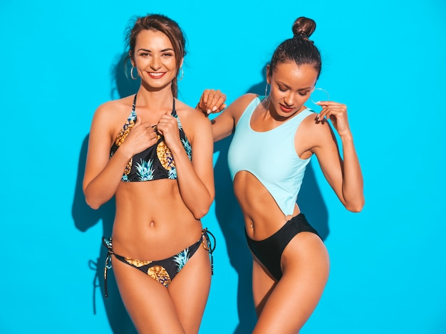 Portrait of two beautiful sexy smiling women in summer swimwear bathing suits. trendy hot models having fun. girls isolated on blue
