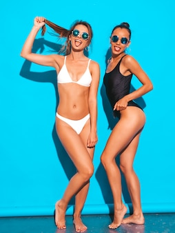 Portrait of two beautiful sexy smiling women in summer white and black swimwear bathing suits. trendy hot models having fun. girls isolated on blue.playing with hair in sunglasses