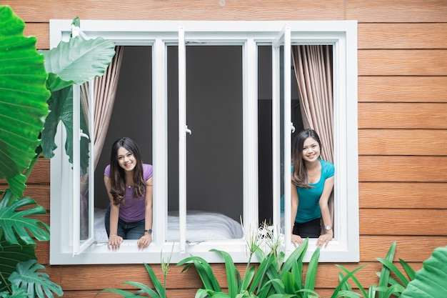 Portrait of two beautiful twin sister at home standing by the window together