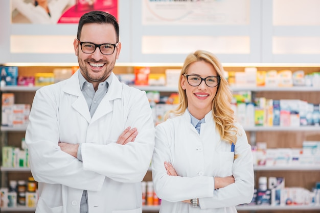 Portrait of a two beautiful young pharmacists at workplace.