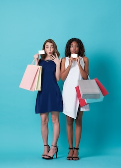 Portrait of two beautiful young woman  showing credit card and shopping bag isolated over blue background.