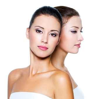 Ritratto di due belle giovani donne isolate su bianco
