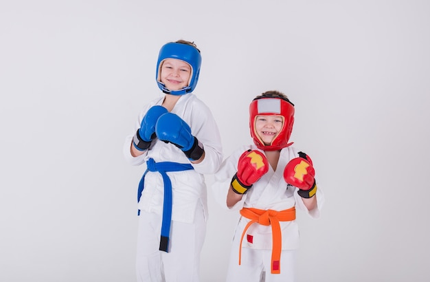 Portrait of two boys in white kimono, helmet and gloves standing in a pose on a white background