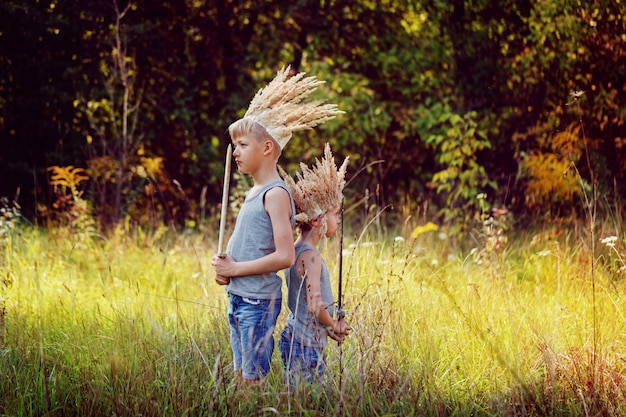 Portrait two brothers have a crown from dry grass on the head and swords in hands. joy and play concept