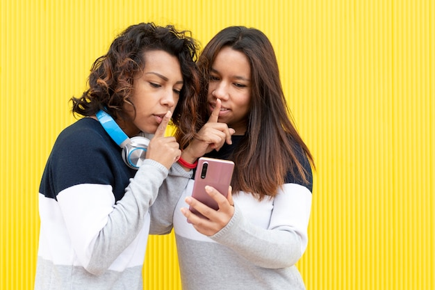 Portrait of two brown girls on a yellow background. both are making the gesture of asking for silence while looking at a smart phone. space for text.