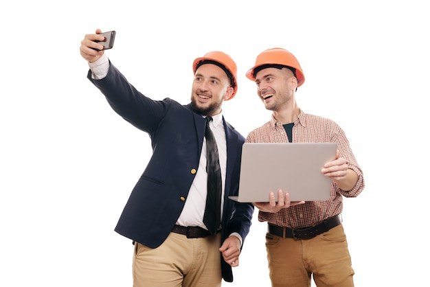 Portrait of two builders in protective orange helmets standing on white isolated background and looking at laptop display. discuss construction project