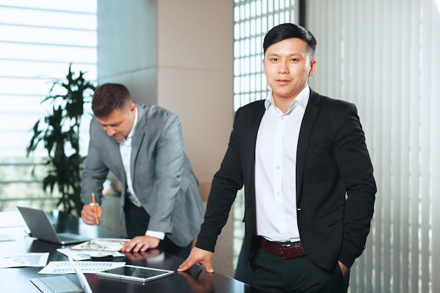 Portrait of two business partners sitting at a table together and working.