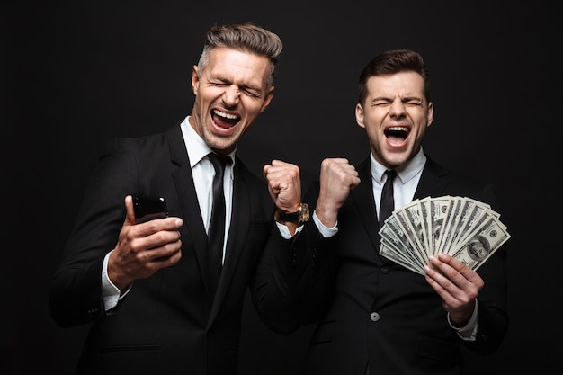 Portrait of two businessmen dressed in formal suit celebrating while holding cellphone and money banknotes isolated over black wall