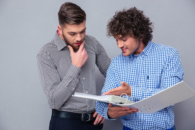 Portrait of a two casual businessmen reading documents in folder over gray wall