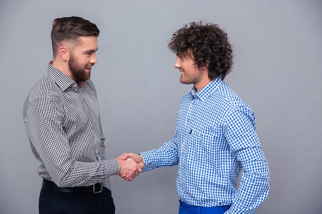 Portrait of a two casual men doing handshake over gray wall