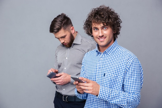 Portrait of a two casual men using smartphone over gray wall