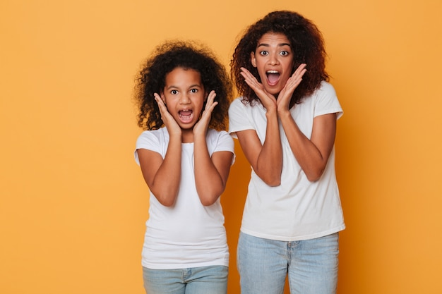 Portrait of two cheerful african sisters screaming