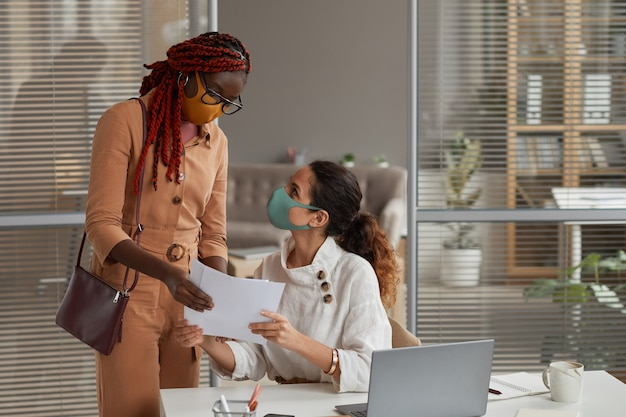 Portrait of two cheerful businesswomen wearing masks while discussing documents in office, copy space