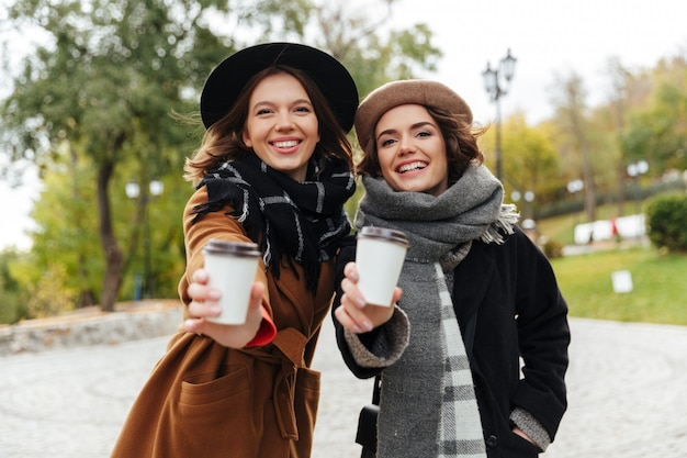 Portrait of two cheerful girls dressed in autumn clothes