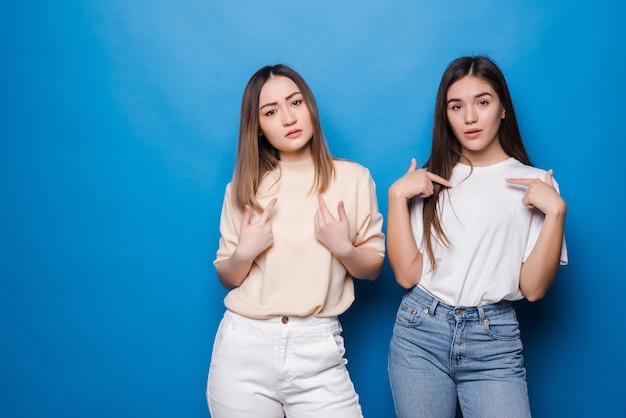 Portrait of two cheerful young women standing together and pointing finger themself isolated over gray wall