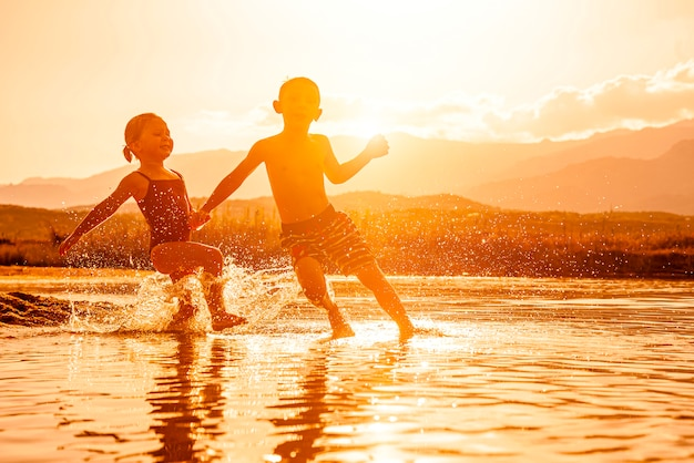 Portrait of two children aged 3 and 6 playing in the sea and spraying water around them.