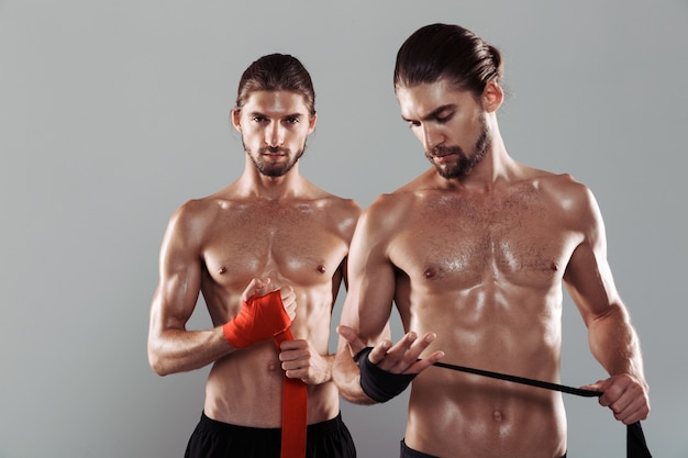 Portrait of a two confident muscular shirtless twin brothers