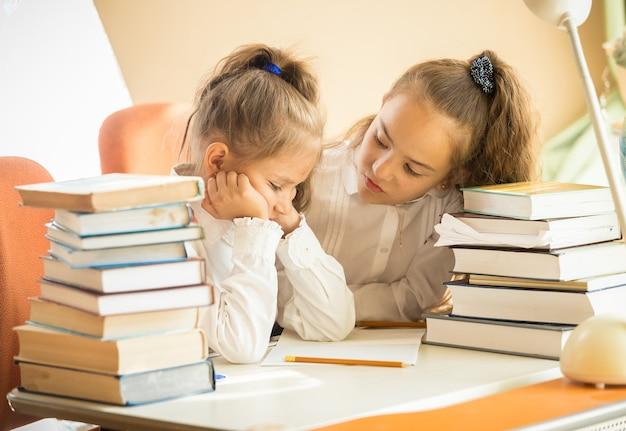 Portrait two cute girls being sad of hard homework