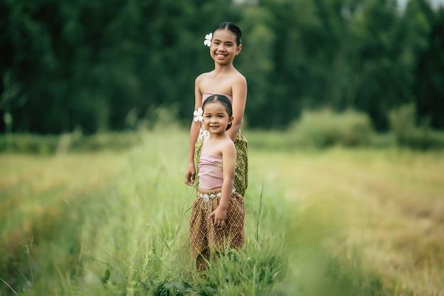 Ritratto di due ragazze carine in abito tradizionale tailandese che camminano sul campo di riso, sorridono con felicità, copia spazio