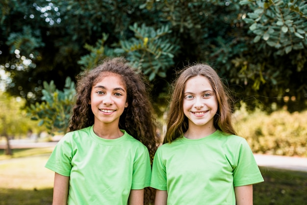 Portrait of two cute girls wearing green t-shirt standing in park