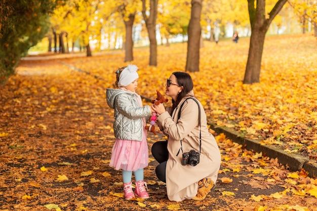 Портрет двух милых счастливых подруг в соломенных шляпах, модных куртках и платьях в солнечный день возле старинных досок на открытом воздухе на природе. улыбающиеся красивые девушки с розовыми волосами наслаждаются отдыхом в сельской местности