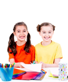 Portrait of two cute little girls in colourful t-shirt cut scissor cardboard - isolated on white.