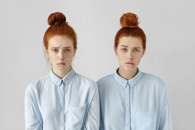 Portrait of two cute redhead student girls wearing same hairstyles and formal shirts biting lips