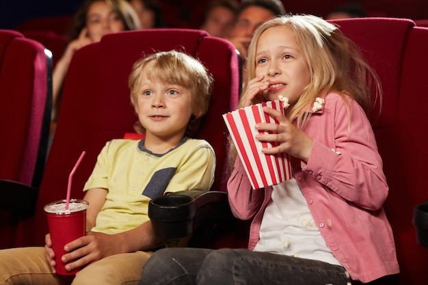 Portrait of two cute scared kids watching movie in cinema theater and eating popcorn, copy space