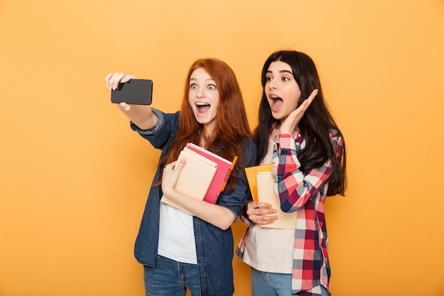 Portrait of two excited young school women