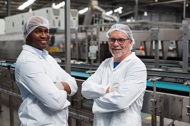 Portrait of two factory engineers standing with arms crossed