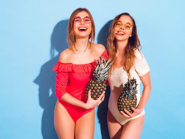 Un ritratto di due modelli castana sorridenti di modo in costumi da bagno dell'estate. ragazze con ananas fresco. donna in occhiali da sole rotondi divertendosi e posando