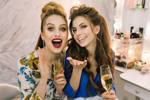 Ritratto due giovani donne felici eccitate alla moda divertendosi, bevendo champagne nel salone di parrucchiere