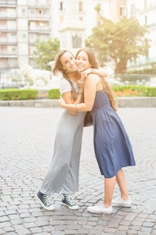 Portrait of two female friends embracing each other standing on pavement