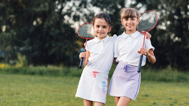 Portrait of two female friends standing with badminton in the park