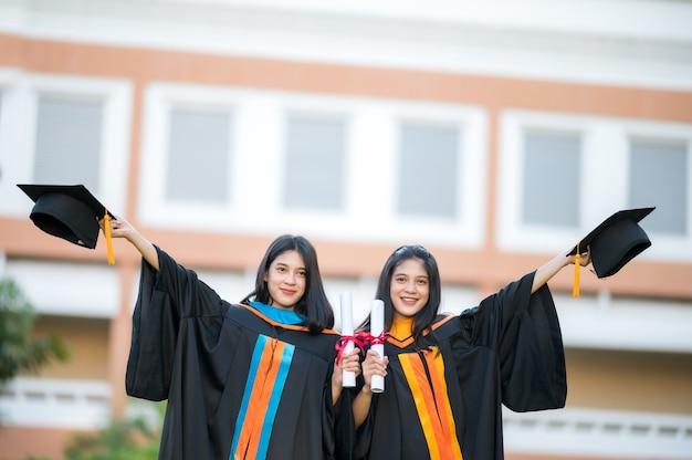 肖像画2人の女性卒業生、大卒者、喜んで帽子を前に持ちます。
