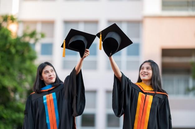 Портрет две выпускницы, выпускницы университетов, с радостью держат шляпы перед собой.