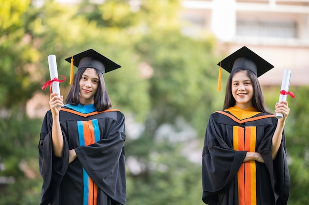 肖像画2つの女性の卒業生、大卒の卒業証書を保持していると幸せ