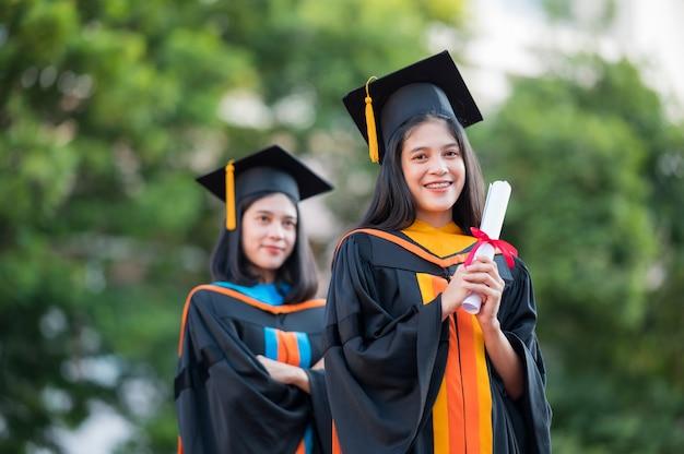 Портрет две женщины-выпускницы, выпускницы вузов с дипломами и счастливые