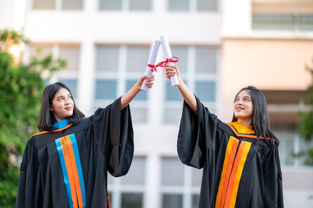 Portrait two female graduates, university graduates holding a diploma and are happy
