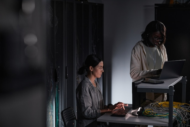 Portrait of two female it engineers working with computer in dark server room, copy space