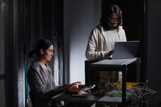 Portrait of two female network engineer using laptop while working in dark server room, copy space