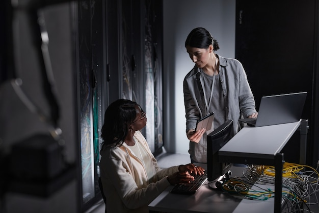Portrait of two female network engineer using laptop while working together in dark server room, copy space