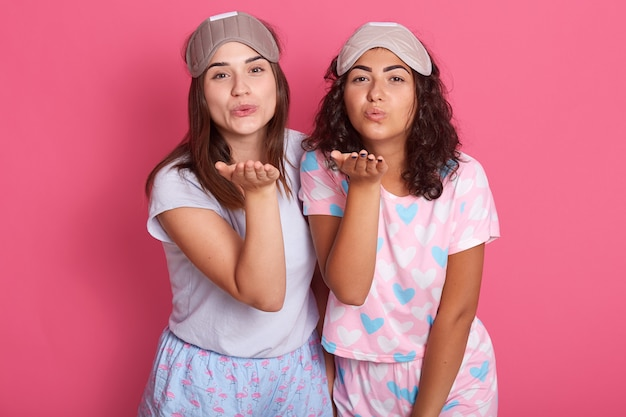 Portrait of two females raising hands, sending blow kiss, going to bed, wearing pajamas and sleeping masks