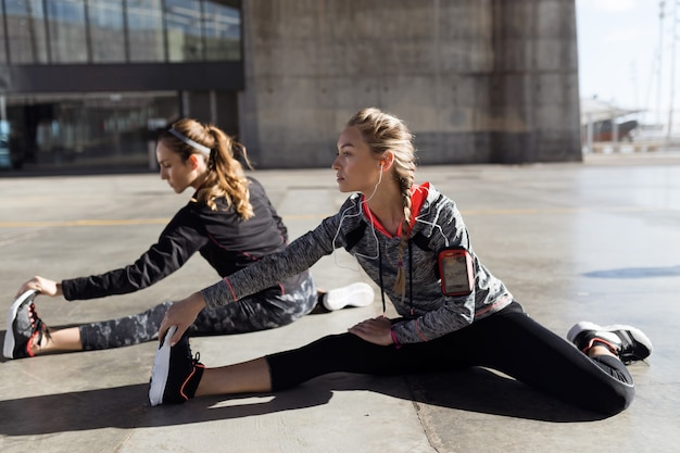 Portrait of two fit and sporty young women doing stretching in city.