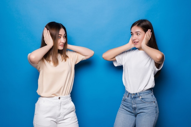 Portrait of two funny mixed race women covering ears isolated over blue wall