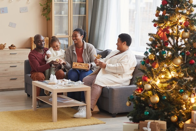 Portrait of two generation african-american family decorating home for christmas together while enjoying holiday season in cozy atmosphere, copy space