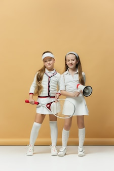 Portrait of two girls as tennis players holding tennis racket