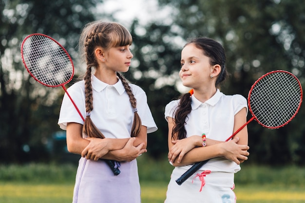 Portrait of two girls holding badminton looking at each other